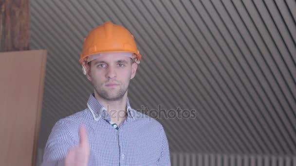 Mladý tvůrce ukázal dobrou kvalitu na budovy ve výstavbě. Zblízka bělošský vousatý muž ukazuje palcem. Stavební dělník v oranžová čepice s úsměvem pro fotoaparát