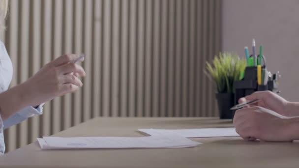 Geschäftsleute unterzeichnen Vertrag bei Firmenversammlung und schütteln Hände.