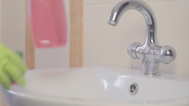 nő csinál házimunkát, a fürdőszobában otthon, takarítás, mosogató és csaptelep spray tisztítószer. Sorozat