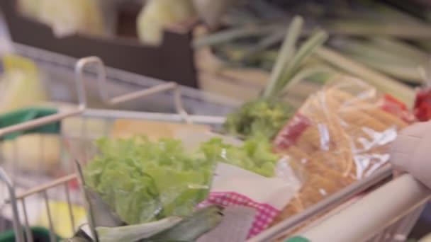 Mladá žena tlačí vozík podél uliček s potravinami v supermarketu. Dívka výběr čerstvé zeleniny v potravin a jejich uvádění do nákupního vozíku