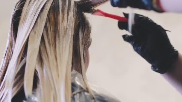 Fodrász stylist teszi a haj színezése, blonding. Ő használja az ecsetet. Nézet bezárásához. Fodrászok fekete kesztyűt kezét. Fodrászat, fodrász szalon