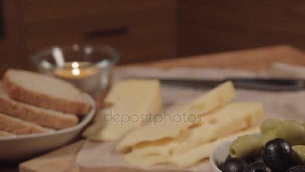 sýr ementál s olivami na dřevěný stůl