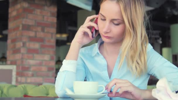 Woman talking on cellphone and drinking cafe latte in cafe