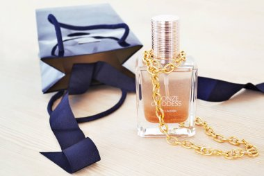 still life photography of Estee Lauder cosmetics with gold chain necklace