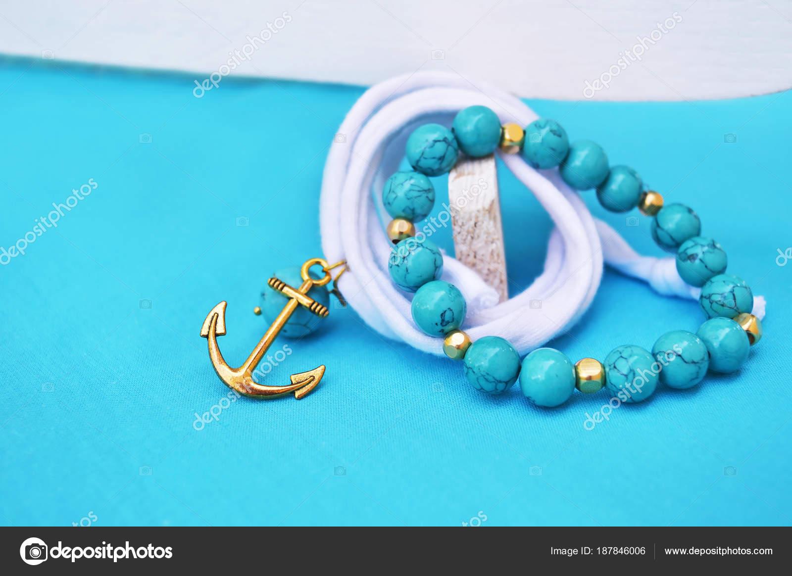 Βραχιόλι - ναυτικά κοσμήματα με άγκυρα χρυσό - τιρκουάζ φόντο τιρκουάζ  ημιπολύτιμες– εικόνα αρχείου feee7476dd5