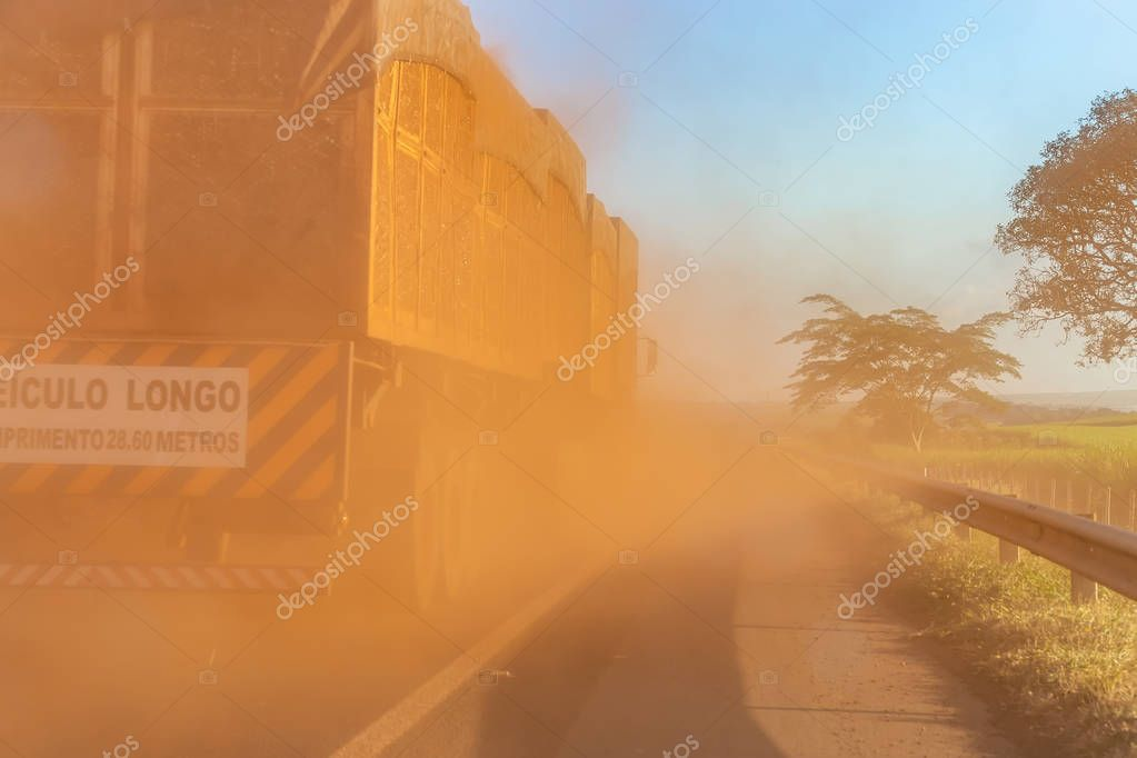 Sugar cane truck on the road with lots of dust