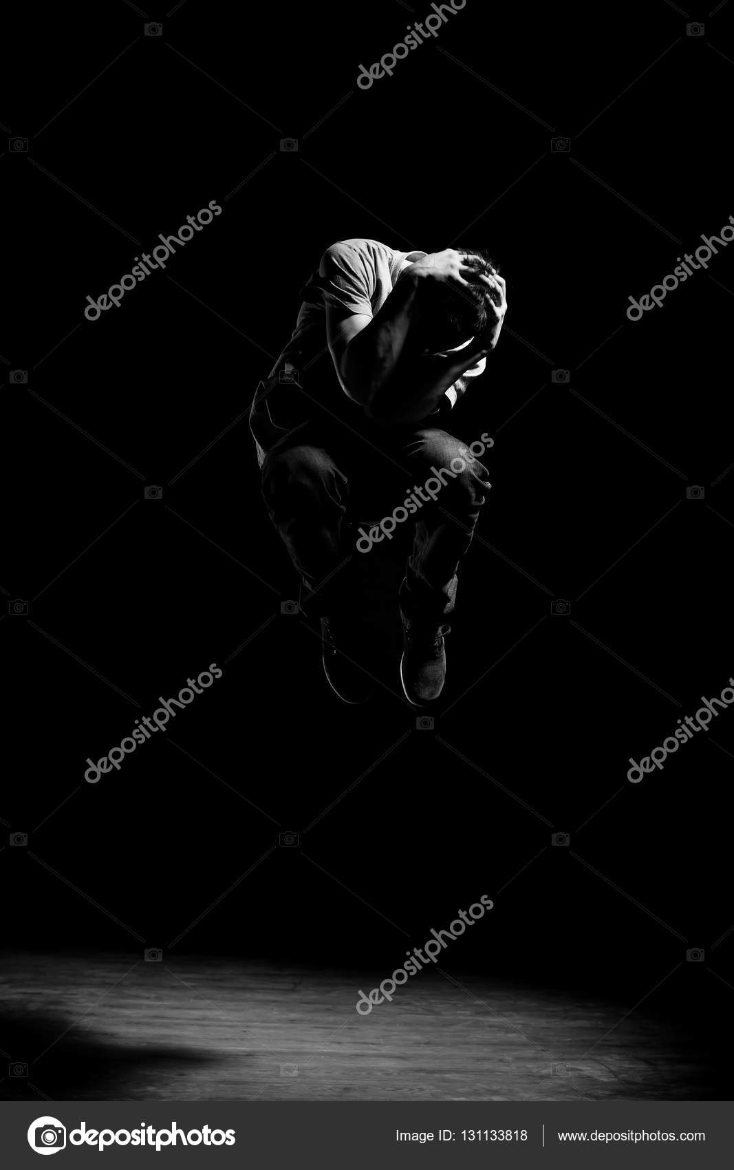 Man in motion on black background studio shot photo by