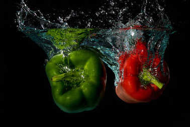 Green & Red Bell Sweet Peppers Droped Into Water