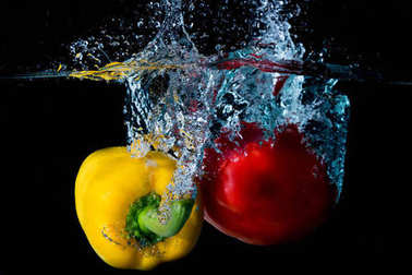 Yellow & Red Bell Sweet Peppers Droped Into Water