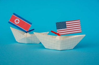 paper ship with Flags of USA and North Korea. conflict in Japanese sea, concept shipment or free trade agreement and membership.