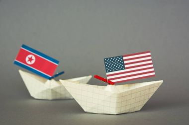 paper ship with Flags of USA and North Korea. conflict in Japanese sea, concept shipment or free trade agreement and membership