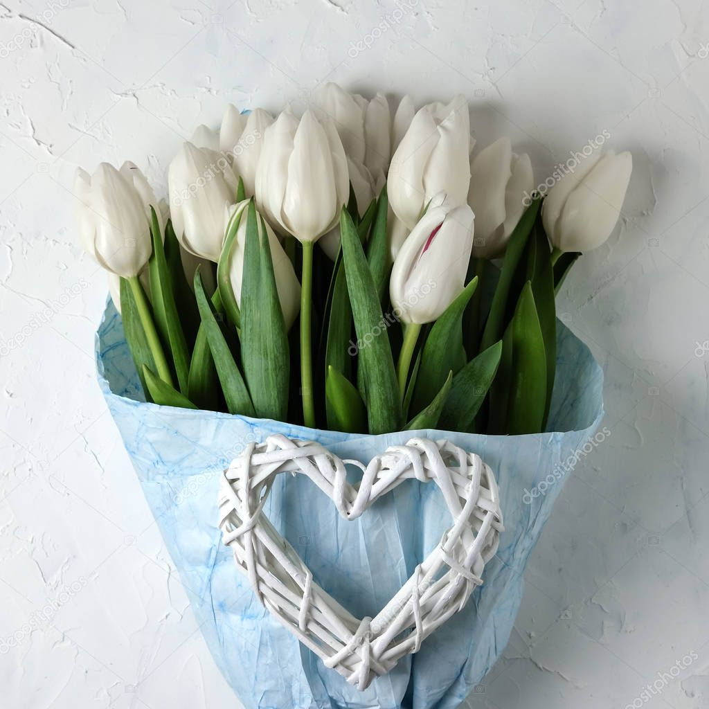 A bouquet of white tulips in blue wrapping paper with woman hands on a white concrete background. Top view. Flat lay. Postcard for Easter, Mothers Day. A square size for social networks.