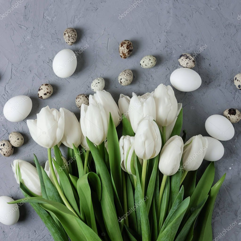 A bouquet of white tulips and chicken and quail eggs on a gray concrete background. Top view. Flat lay. Postcard for Easter and Spring Holidays. A square size for social networks.