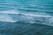 Texture of the sea or ocean with white lamb waves rolling to the shore.