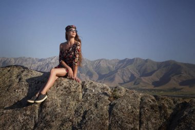 Portrait of a girl model in the mountains in a bright, sunny day