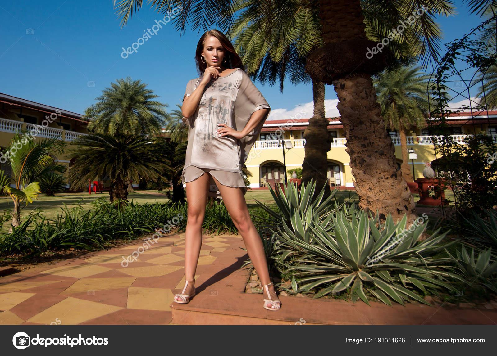 Beautiful, elegant girl, model strolls in a tropical garden near ...