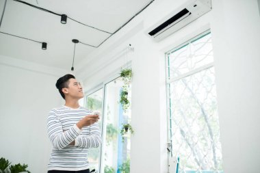 man turning air condition
