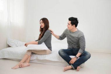 Sad couple sitting in room