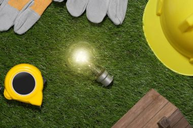 Green building and energy saving concept: house projecj and work tools on the grass