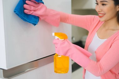 Portrait of attractive young woman cleaning a surface of white kitchen closet