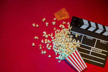 Movie tickets, clapperboard, pop corn on red background