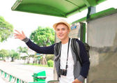 Handsome young asian man waiting bus and smiling