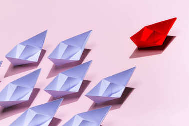 Leadership concept. Red paper ship leading among white on pink background.