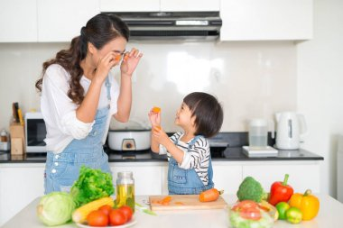 Happy family in kitchen. Mother and child daughter preparing vegetables and fruit.