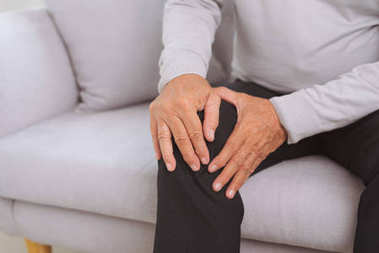 Senior man sitting on sofa in living room at home and touching his knee by the pain