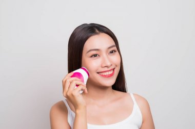 Young asian woman using electric brush for deeply clean
