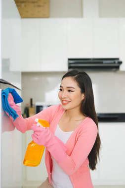 Portrait of attractive young woman cleaning surface of white kitchen closet with detergent spray.