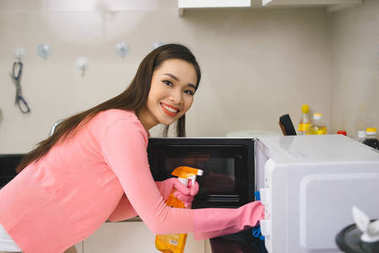 Young asian woman cleaning kitchen with detergent spray.