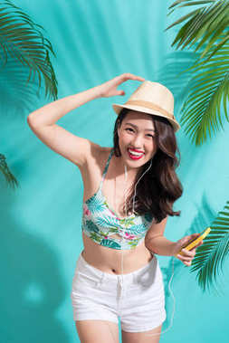 Summer fashion girl in hat standing and smiling over vibrant blue background