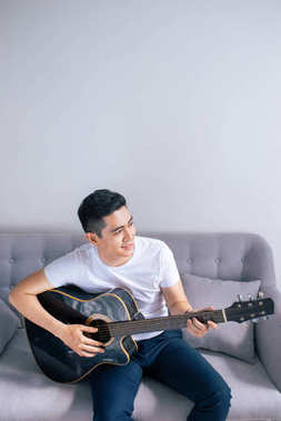 Handsome asian man playing on guitar sitting on couch at home