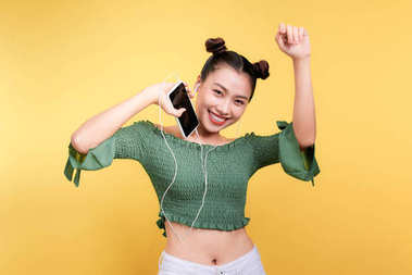 Fashion smiling asian woman listening to music in earphones  over yellow background