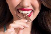 Fotografie Nahaufnahme von Frau mit rotem Lippenstift, Schokolade zu essen