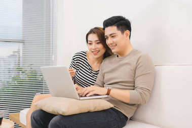 Happy asian couple in love surfing on laptop at home