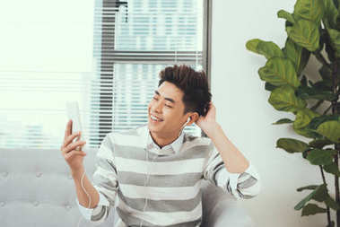 Smiling asian handsome man sitting on cosy sofa listening to music