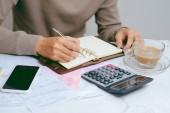 Male ruce, dělá finance a vypočítat náklady na domácí kancelář