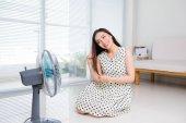 Fényképek Gyönyörű Éva nő ül a nappaliban padló élvezi elektromos ventilátor hűvös szél