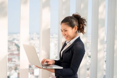 A shot of businesswoman working on her laptop outdoor