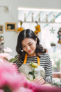 Young beautiful asian girl florist taking care of flowers at workplace.