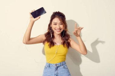 Portrait of a cheerful beautiful girl showing or presenting mobile phone application and pointing finger to sky