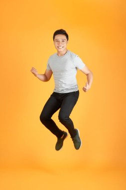 Energetic happy young Asian man in casual clothes jumping, studio shot isolated in orange background stock vector