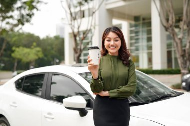 Wonderful day. Positive smiling young woman standing near a new electric car with a cup of coffee in her hands