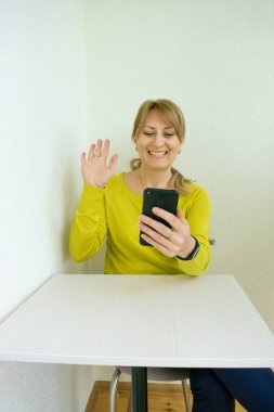 Smiling woman with smartphone communicates in online chat and social networks while at home on white loggia background ones during quarantine and social distance at Coronovirus pandemic. Home leisure.