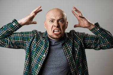 Angry rage young man shouting over beige background.