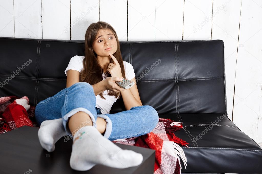 chica guapa aburrida viendo la televisi n sentado en el sof en casa fotos de stock nk. Black Bedroom Furniture Sets. Home Design Ideas