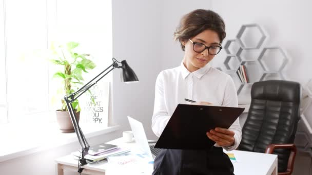 Attractive businesswoman writing in folder smiling showing okay in office