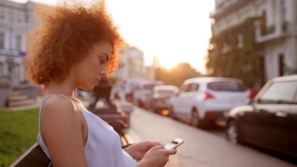 Hezká dívka psaní na telefonu sedí na lavičce v městském parku v západu slunce Zpomalený pohyb